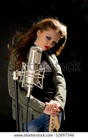 Girl in green jacket holding microphone - stock photo