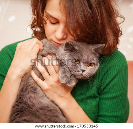 girl in green sweater embraces gray British cat - stock photo