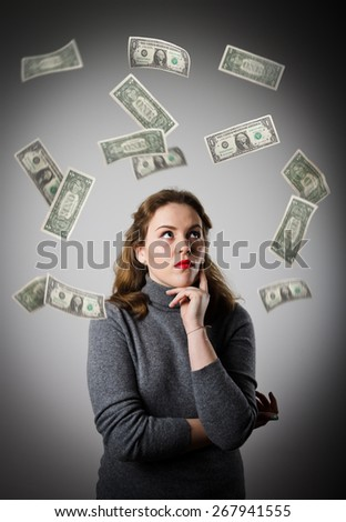 Girl in grey and falling dollar banknotes. Currency and lottery concept. - stock photo