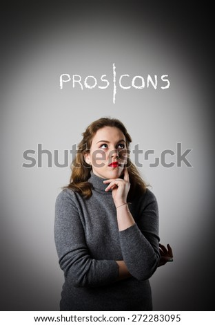 Girl in grey is thinking. Pros and cons concept. - stock photo