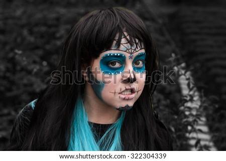 Girl in Halloween makeup - mexican Santa Muerte mask - stock photo