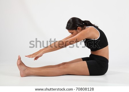 Girl in hamstring stretch to touch toes - stock photo