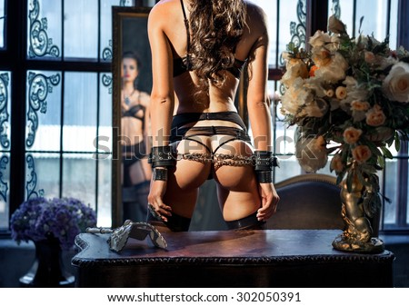 Girl in handcuffs looks in vintage interior - stock photo