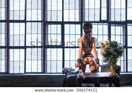 Girl in handcuffs, standing in a large room across from the huge windows. - stock photo
