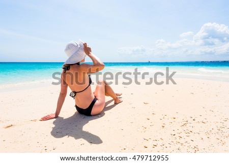 girl in hat and black swimsuit sitting on beautiful beach with blue ocean and sky on the background