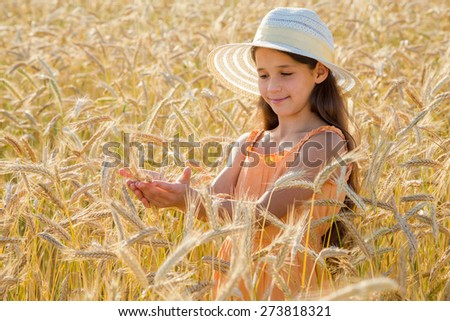Girl in hat looking to spica of wheat in hands, standing on field - stock photo