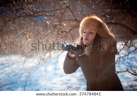girl in hat with ear flaps blowing on the snow