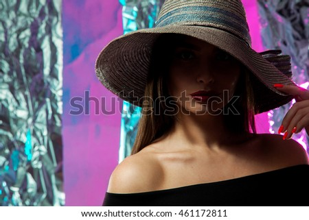 girl in hat with wide brim and red lips posing in studio on multicolor background