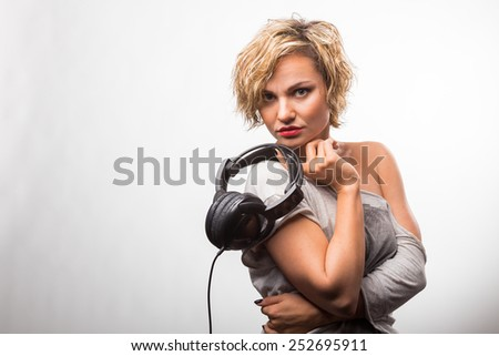 Girl in headphones. Blonde listening to music on stereo headphones. Emotions while listening to music. - stock photo