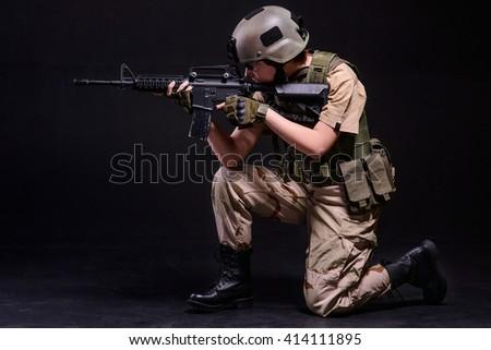 Girl in helmet aiming from gun on black background/Girl in helmet aiming from rifle - stock photo