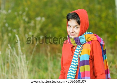 Girl in hood with multi-colored scarfs on autumn background. - stock photo