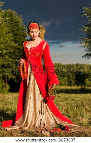 Girl in Italian renaissance dress and mask on sunset time - stock photo