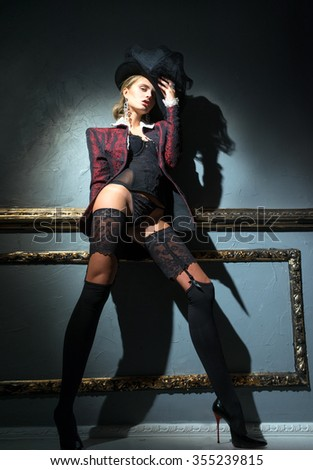 Girl in jacket and lingerie posing near the wall