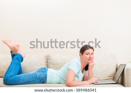 girl in jeans and a T-shirt on the couch with a laptop - stock photo