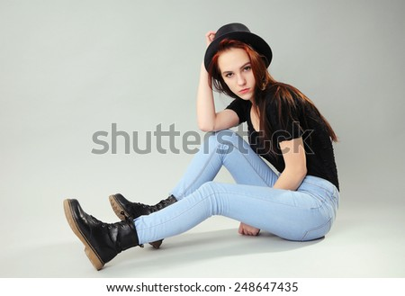 Girl in jeans, boots, hat and black t-shirt sitting on the floor - stock photo