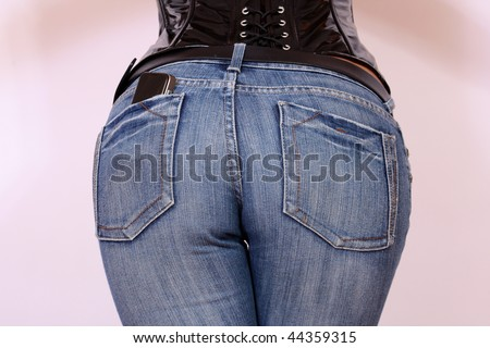 Girl in jeans from behind with cell phone in her pocket - stock photo