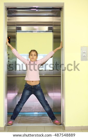 Girl in jeans holding the elevator door and kicking