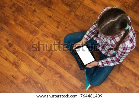 girl in jeans sits on the wooden floor and holding a black tablet pc with blank white screen. Concept of teenage life and gadgets. Top view with copy space.