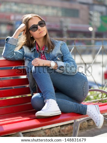 girl in jeans sitting on a bench on a city street - stock photo