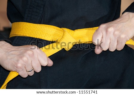 Girl in karate gi tightening yellow belt - stock photo
