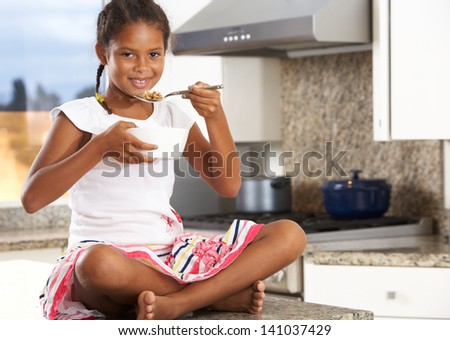 Girl In Kitchen Eating Bowl Of Breakfast Cereal - stock photo