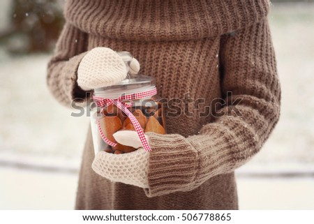 girl in knitted sweater and mittens holding in hands a jar with homemade gingerbread cookies outdoors on snowy background. sweet cozy winter time. winter wonderland. winter still life. christmas card
