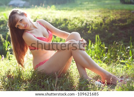 Girl in lacy lingerie on the meadow in the sunlight