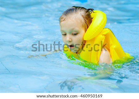 girl in life jacket swimming in the pool