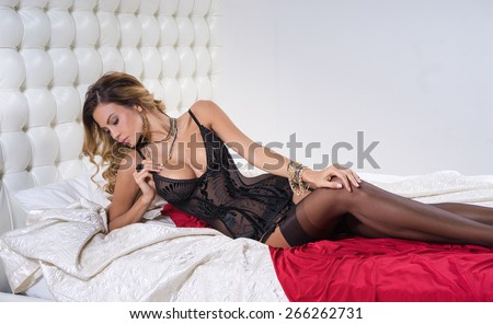 Girl in lingerie lying on the bed  - stock photo