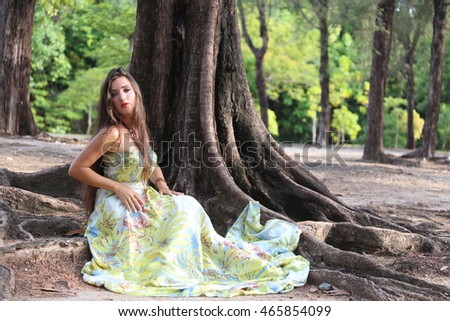 girl in long dress in the forest, young woman in full-length dress sitting near the tree's root,aphrodite in forest