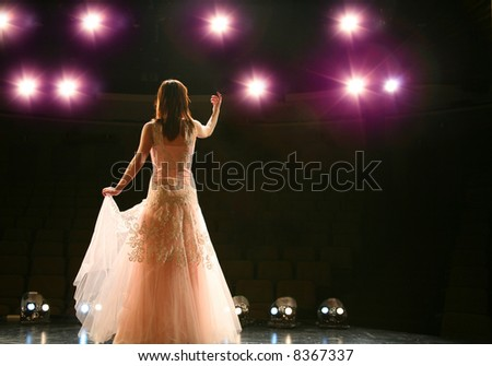 girl in long gown performing on stage