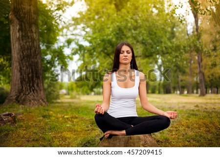 Girl in lotus position relaxing in the forest