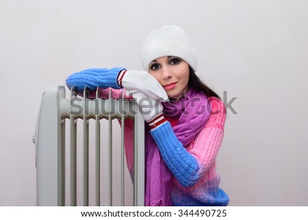 Girl in mittens and hats bask near radiator