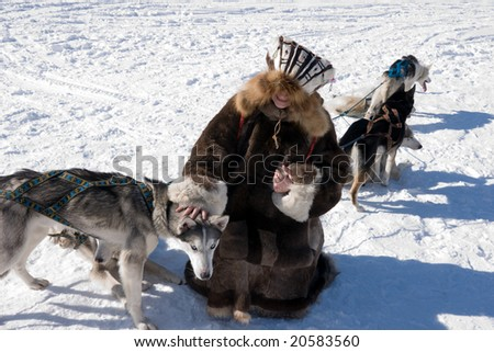 girl in national gown pets the dog Haska - stock photo