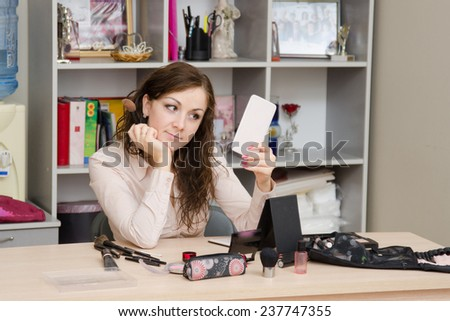 Girl in office looks the mirror