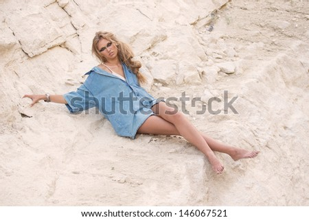 Girl in oversize t-shirt over stone-pit background, outdoor shoot - stock photo