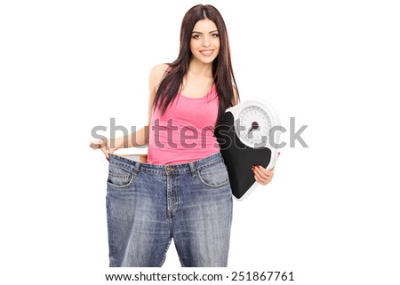 Girl in oversized jeans holding a weight scale isolated on white background - stock photo