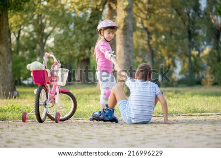 girl in park, helps boy with roller skates to stand up - stock photo