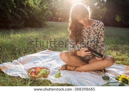 Girl in park listening old radio and smiling - stock photo