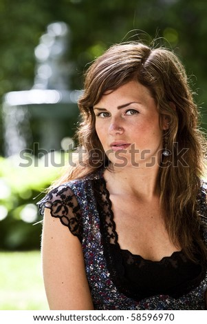 Girl in park, looking into the camera. - stock photo