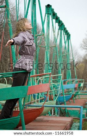 Girl in park on  old swing. Breathes fresh spring air.