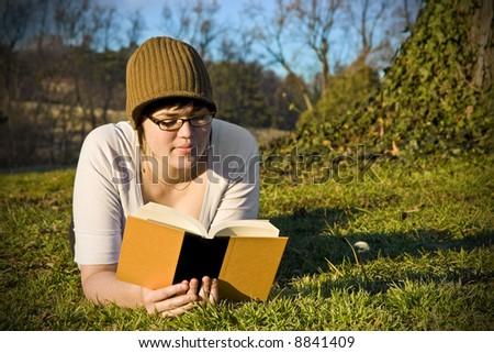 Girl in park reading book - stock photo
