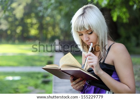 girl in park with  book.  student. Summer day. - stock photo