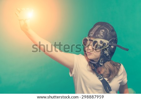 Girl in pilot helmet meking a selfie by smartphone