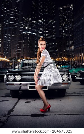 Girl in pin-up on a background of retro cars. night city  - stock photo