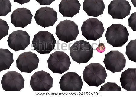Girl in pink alone amongst black umbrellas - stock photo