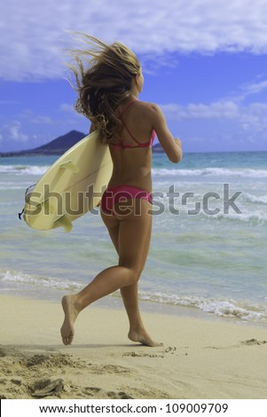 girl in pink bikini with surfboard running to the ocean