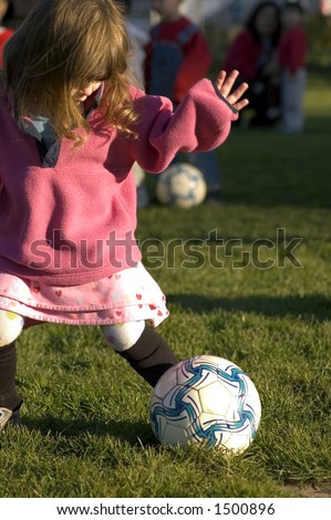 girl in pink clothes kicking soccer ball - stock photo