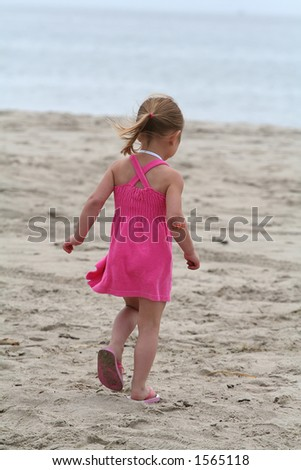 Girl in pink dress at the beach
