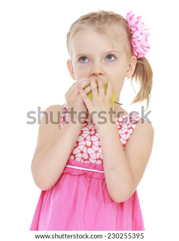 Girl in pink dress eating Apple.Very cheerful little girl. - stock photo